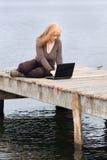 Donna di Redhead con il computer portatile sul pilastro Immagini Stock