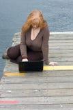 Donna di Redhead con il computer portatile sul pilastro Fotografia Stock