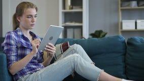 Donna di rilassamento che si siede e Internet di lettura rapida sulla compressa video d archivio