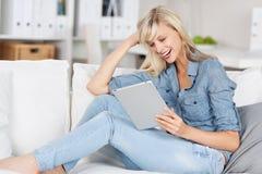 Donna di risata che esamina la sua compressa Immagine Stock Libera da Diritti
