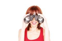 Donna di risata che osserva tramite il binocolo fotografia stock