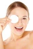 Donna di risata che tiene un cuscinetto di cotone al suo occhio Immagine Stock