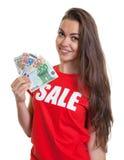 Donna di risata con capelli marroni lunghi in camicia di vendita con soldi Fotografie Stock Libere da Diritti