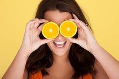 Donna di risata con le fette arancioni sopra gli occhi Fotografia Stock