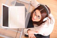 Donna di risata con un computer portatile e le cuffie Immagine Stock