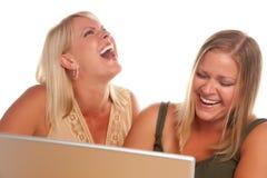 Donna di risata due che per mezzo del computer portatile Immagine Stock Libera da Diritti