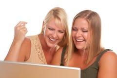 Donna di risata due che per mezzo del computer portatile Fotografie Stock Libere da Diritti