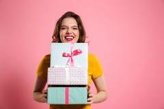 Donna di risata felice con le labbra rosse che tengono mazzo di contenitori di regalo, immagini stock libere da diritti