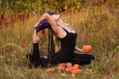 Donna di risata nell'yoga di pratica del costume della strega Immagini Stock Libere da Diritti