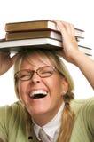 Donna di risata sotto la pila di libri sulla testa Immagine Stock Libera da Diritti
