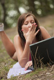 Donna di sbadiglio con il computer portatile in foresta Fotografie Stock Libere da Diritti