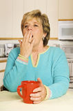 Donna di sbadiglio con la tazza di caffè rossa nella sua cucina Fotografia Stock