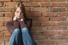Donna di seduta della testarossa davanti al muro di mattoni Fotografia Stock