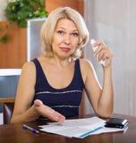 Donna di Serios che compila i documenti finanziari fotografia stock