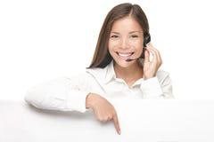 Donna di servizio di assistenza al cliente che mostra il segno del tabellone per le affissioni Fotografia Stock