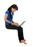 Donna di smiley con seduta del computer portatile. Fotografie Stock Libere da Diritti