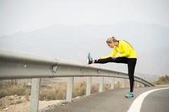 Donna di sport che allunga il muscolo della gamba dopo l'allenamento corrente sulla strada asfaltata con il paesaggio asciutto de Immagine Stock
