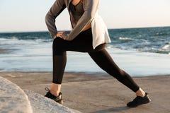 Donna di sport che fa esercizio di allungamento alla spiaggia Fotografia Stock