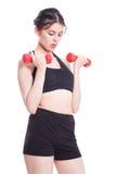 Donna di sport che fa esercizio con i pesi di sollevamento Fotografia Stock
