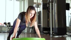 Donna di sport che fa gli esercizi con una palla dell'equilibrio alla palestra archivi video