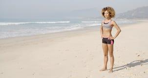 Donna di sport che sta sulla spiaggia video d archivio