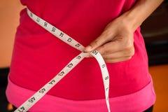 Donna di sport con nastro adesivo di misurazione su uno snello la sua vita immagine stock libera da diritti