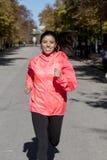 Donna di sport del corridore nel funzionamento e nell'addestramento degli abiti sportivi di autunno sopra Fotografia Stock Libera da Diritti