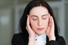 Donna di stanchezza di sforzo di emicrania che massaggia le tempie immagini stock