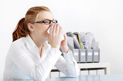Donna di starnuto nell'ufficio. Fotografia Stock Libera da Diritti