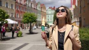 Donna di stile in occhiali da sole e gelato nel quadrato invecchiato del centro urbano archivi video