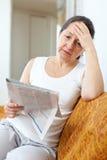 Donna di tristezza con il giornale immagini stock