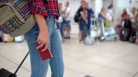 Donna di viaggio in camicia casuale con il bagaglio che tiene un passaporto in sua mano che cammina nel terminale di aeroporto mo video d archivio