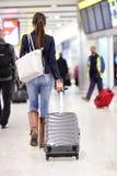 Donna di viaggio che cammina in un aeroporto con bagagli Fotografia Stock