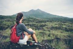 Donna di viaggio che si siede vicino alla montagna e che guarda lontano Immagini Stock Libere da Diritti