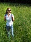 Donna di viaggio con lo zaino che esamina prato alpino il giorno soleggiato Immagini Stock Libere da Diritti