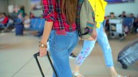 Donna di viaggio dei giovani in camicia casuale con il bagaglio che cammina nel terminale di aeroporto moderno Primo piano Vista  stock footage