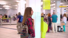 Donna di viaggio dei giovani in camicia casuale con il bagaglio che cammina nel terminale di aeroporto moderno Vista dalla parte  video d archivio
