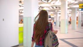 Donna di viaggio dei giovani in camicia casuale con il bagaglio che cammina nel terminale di aeroporto moderno Vista dalla parte  stock footage