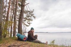 Donna di viaggio sola che si siede vicino al lago della foresta e che guarda lontano Fotografia Stock
