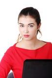 Donna di vista frontale che si siede allo scrittorio con il computer portatile Fotografia Stock Libera da Diritti