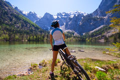 Donna di Yaung che guida una bici al lato del lago alpino Immagini Stock