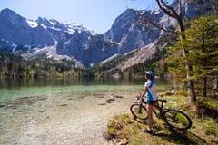 Donna di Yaung che guida una bici al lato del lago alpino Fotografie Stock