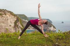 Donna di yoga Asana esteso di posa del triangolo sulla scogliera vicino all'oceano Fotografie Stock Libere da Diritti