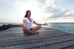Donna di yoga che meditating vicino al mare Immagine Stock