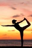 Donna di yoga nel tramonto sereno alla spiaggia che fa posa Immagine Stock