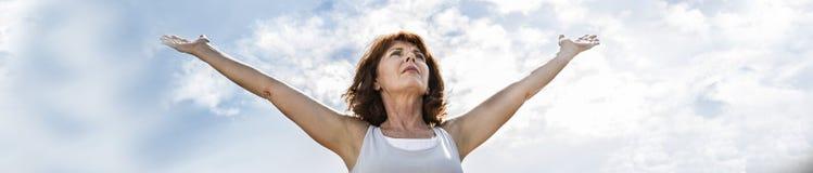 donna di yoga 50s che apre armi all'esercizio, meditazione di pratica Immagini Stock