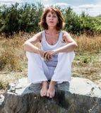 donna di yoga 50s che si siede sulla pietra che si rilassa per la pace spirituale Fotografie Stock Libere da Diritti