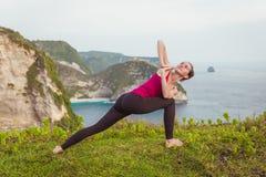 Donna di yoga sulla scogliera vicino all'oceano Fotografie Stock Libere da Diritti