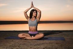 Donna di yoga sulla spiaggia al tramonto Fotografie Stock