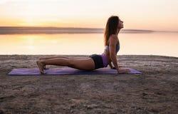 Donna di yoga sulla spiaggia al tramonto Fotografia Stock